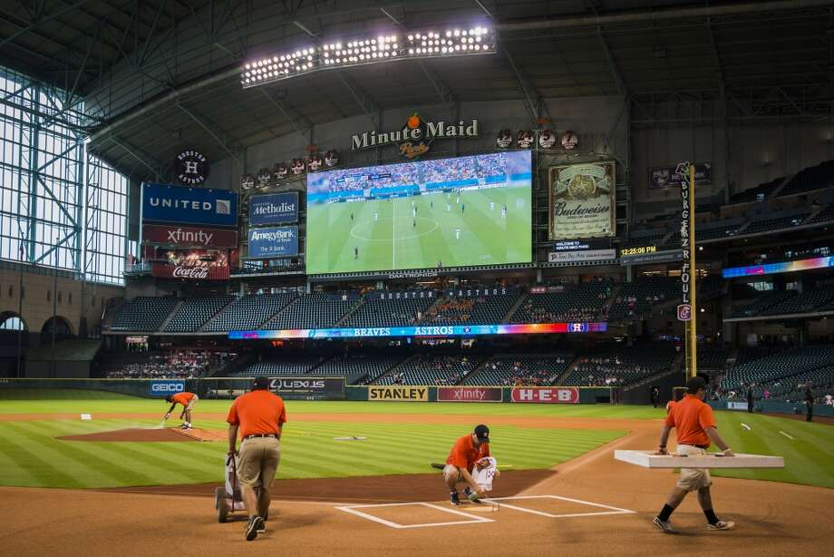 The USA soccer game against Germany in World Cup soccer action shows on video screens at Minute Maid Park as groundskeepers prepare the field before the Astros game. Photo: Smiley N. Pool, Houston Chronicle