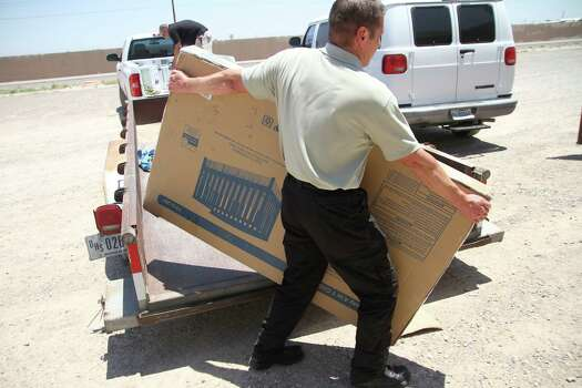 A federal employee unloads a crib outside of the barracks for law enforcement trainees turned into immigrant detention center at the Federal Law Enforcement Center (FLETC) in Artesia, N.M., Thursday, June 26,  2014. Federal officials say this federal training center that is home to the Border Patrol Academy that will become a 672-bed detention center for adult immigrants who entered the country illegally and are accompanied by children.  (AP Photo/Juan Carlos Llorca) Photo: Juan Carlos Llorca), Associated Press / AP