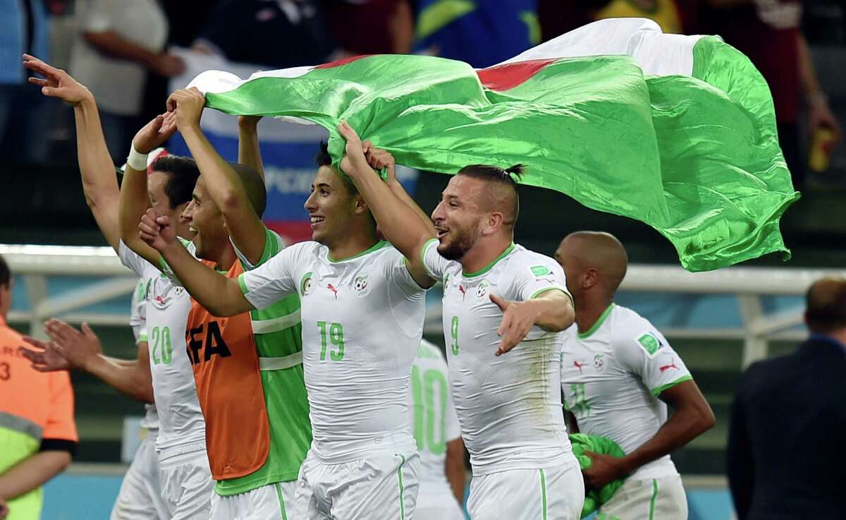 Algerian players celebrate after the group H World Cup soccer match between Algeria and Russia at the Arena da Baixada in Curitiba, Brazil, Thursday, June 26, 2014. The match ended in a 1-1 draw, but Algeria qualified for the round of 16. (AP Photo/Martin Meissner)