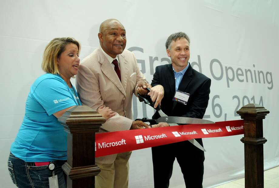 Sabrina Dziubarczyk, Mall Microsoft Retail Store Manager, from left, championship boxer George Foreman, and Lane Sorgen, Microsoft General Manager for South Central US, cut the ceremonial ribbon during the Microsoft Retail Store Opening event in The Woodlands Mall on Thursday. Photo: Jerry Baker, For The Chronicle