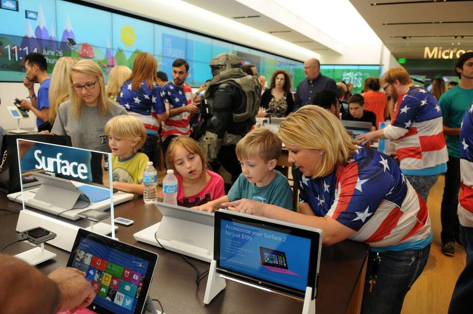 Sabrina Dziubarczyk, Mall Microsoft Retail Store Manager, from right, with Hayden Hammons, 5, of Magnolia, friend Karyme Serna, 6, his brother Zachary, 8, and the boy's nanny, Faith McDaniel, also of Magnolia, check out the Surface Tablets during the Microsoft Retail Store Grand Opening event in The Woodlands Mall on Thursday. Photo: Jerry Baker, For The Chronicle