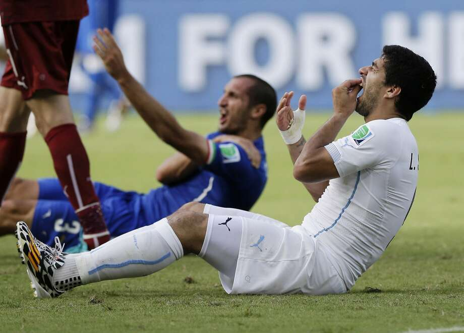 Luis Suarez, checking his teeth after chomping on Giorgio Chiellini, was given a lengthy ban from soccer by FIFA. Photo: Ricardo Mazalan, Associated Press