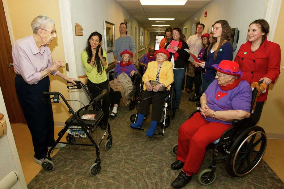 Ella Siems, left, visits with a group of Christmas carolers as they sing down the hallways of the Manor Care Center in Willowbrook on Wednesday, Dec. 25, 2013, in Houston. The volunteers were from a group called the Holiday Project.  For seventeen years, the Holiday Project has visited Houston area nursing homes and hospitals to spread Holiday cheer for patients that might have thought they were forgotten.  ( J. Patric Schneider / For the Chronicle ) Photo: J. Patric Schneider, Freelance / © 2013 Houston Chronicle