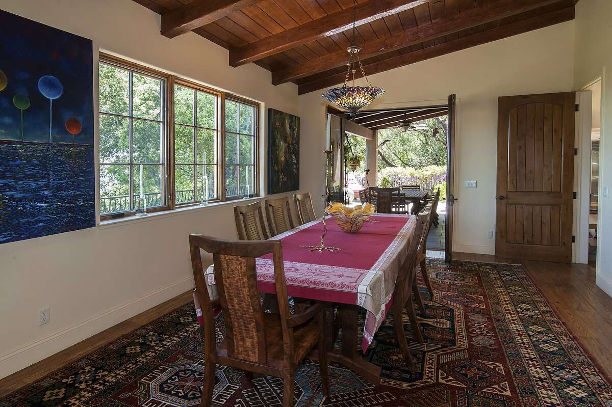 The formal dining room is illuminated by large windows and a chandelier and opens to an outdoor dining area.