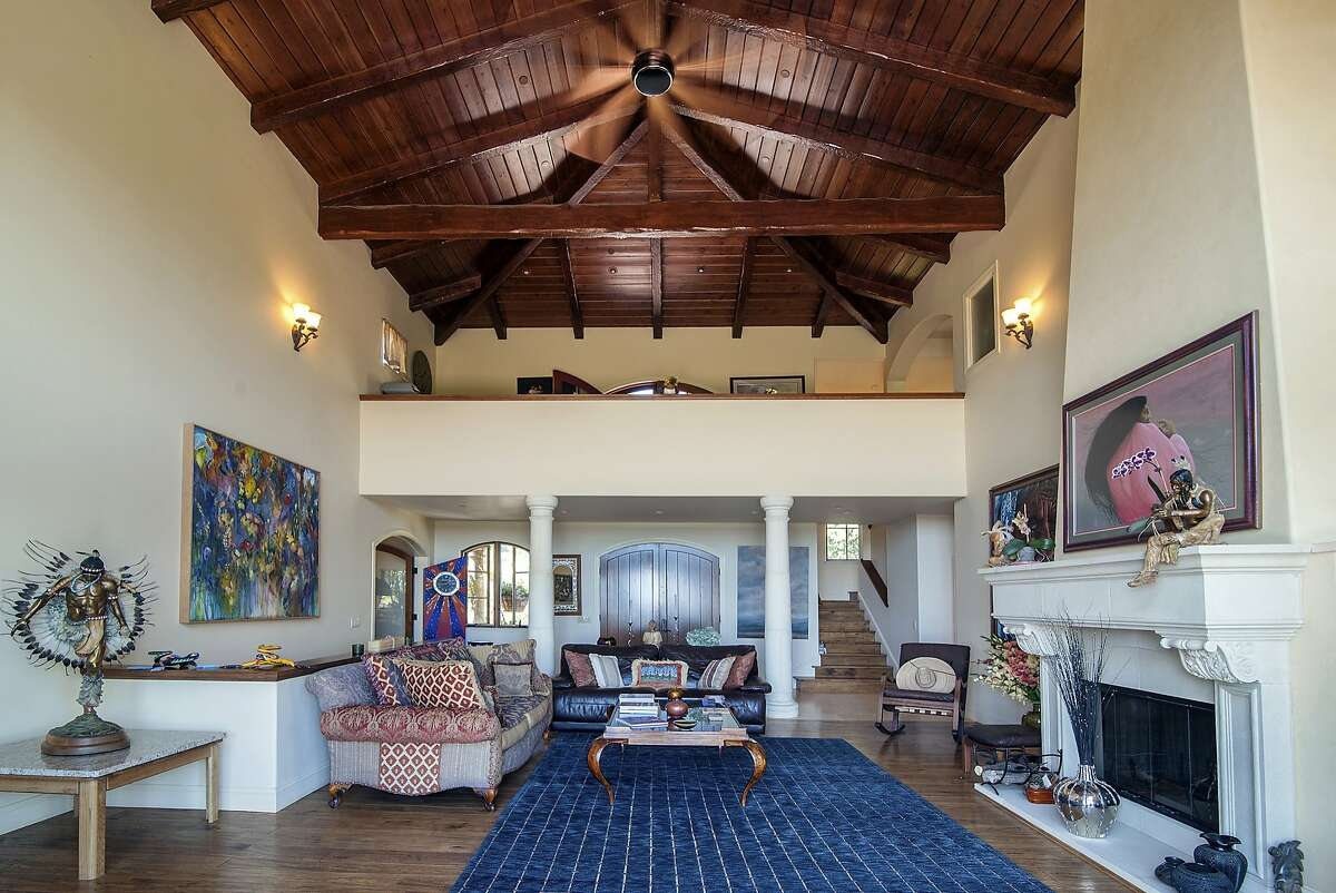 The living room features a beamed ceiling, mezzanine and dual arched entry doors.