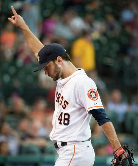Astros righthander Jarred Cosart, acknow-ledging the crowd at Minute Maid Park on Thursday as his afternoon ends after seven innings, tied Dallas Keuchel for the team lead in victories, beating the Braves for No. 8. Last season, no Astros pitcher won more than seven games. Photo: Smiley N. Pool / © 2014  Smiley N. Pool