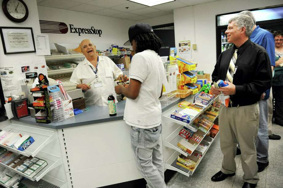 Shop owner Mike Mercado, left, laughs with customers at Mercado's News Express Stop on Wednesday, June 25, 2014, at the State Education Building in Albany, N.Y. Mercado, who is blind, will close his shop after 35 years of operation on Friday. (Cindy Schultz / Times Union) Photo: Cindy Schultz / 00027512A