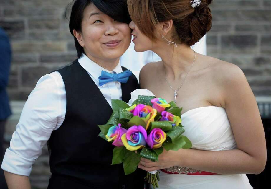 Jen Chang, left, and Inae Lee pose for photos before joining over 100 gay couples in a mass wedding during World Pride 2014 at Casa Loma in Toronto, Thursday, June 26, 2014. Photo: Darren Calabrese, Associated Press / CP