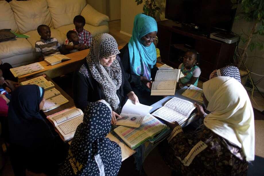 Surrounded by students, Amina Meliani, center left, and Sofiyyah Abdulwahab, center right, recite sections of the Quran for teacher Zenab Hamdan. Photo: Johnny Hanson, Staff / © 2014  Houston Chronicle