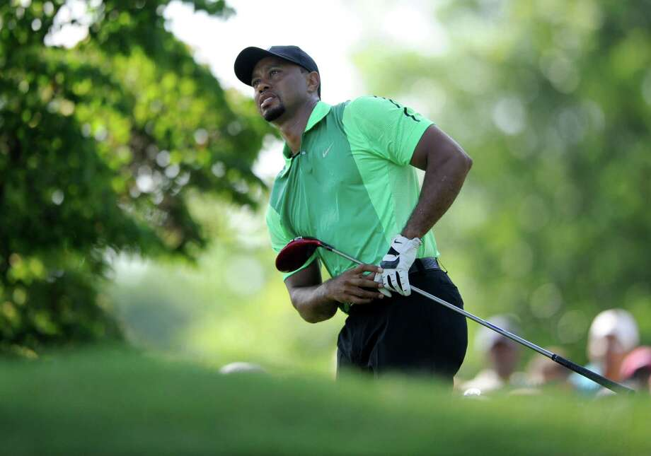 Tiger Woods watches his tee shot on the 15th hole during the first round of the Quicken Loans National golf tournament, Thursday, June 26, 2014, in Bethesda, Md. (AP Photo/Nick Wass) ORG XMIT: MDNW107 Photo: Nick Wass / FR67404 AP