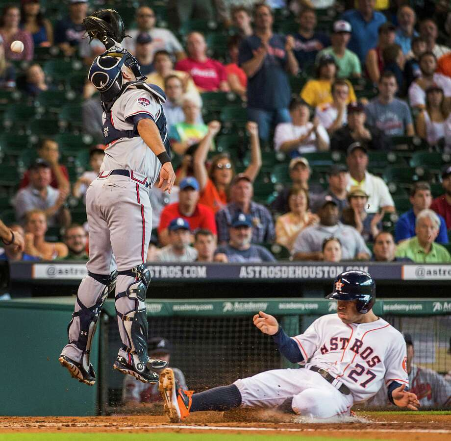 Houston Astros second baseman Jose Altuve (27) scores on a double by Jon Singleton as the throw gets away from Atlanta Braves catcher Gerald Laird (11) during the first inning at Minute Maid Park on Thursday, June 26, 2014, in Houston. ( Smiley N. Pool / Houston Chronicle ) Photo: Smiley N. Pool / © 2014  Smiley N. Pool