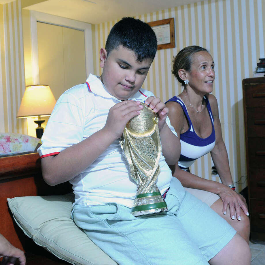 11-year-old David Tovar Jr. holds his replica of the World Cup trophy as his mother, Libby Tovar, sits by his side, while the pair were watching and listening to the World Cup soccer match between Germany and the United States at their Greenwich home, Thursday, June 26, 2014. David Jr. is blind and a Special Olympic athlete who loves the World Cup Soccer Tournament. Although Team USA lost 1-0 to Germany, they still advanced to the knockout stage of the tournament called the round of sixteen. Photo: Bob Luckey / Greenwich Time