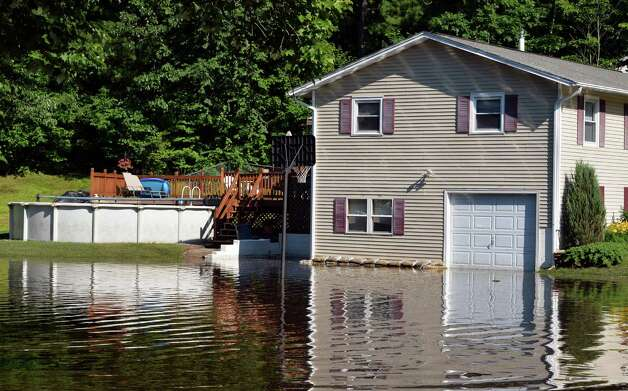 Flood waters from Wednesday's downpour reaches a home on New Castle Road Thursday, June 26, 2014, in Halfmoon, NY.  (John Carl D'Annibale / Times Union) Photo: John Carl D'Annibale / 00027522A