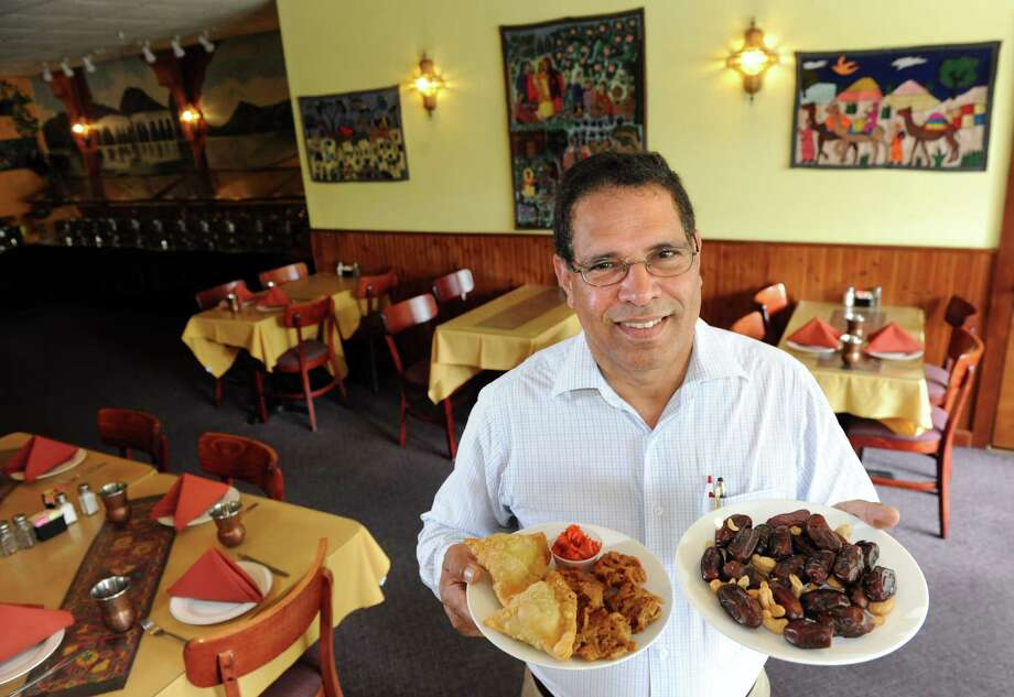 Restaurant owner Qasim Bhatti holds a plate of dates, right, and a plate of samosas and pakora with onion chutney on Thursday, June 26, 2014, at Lazeez in Albany, N.Y. Dates are traditionally eaten to break the dawn to dusk fast of Ramadan. (Cindy Schultz / Times Union) Photo: Cindy Schultz / 00027518A