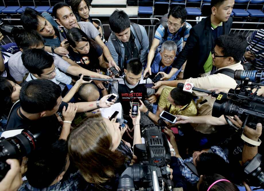 The Houston Rockets' Jeremy Lin is interviewed by a horde of reporters during a break in his team's practice at the Mall of Asia Arena at suburban Pasay city, south of Manila, Philippines, Tuesday Oct. 8, 2013. Lin has easily stolen the spotlight as the Houston Rockets practice for this week's first ever NBA preseason game against the Indiana Pacers in the basketball-obsessed Philippines. (AP Photo/Bullit Marquez) Photo: Bullit Marquez, Associated Press