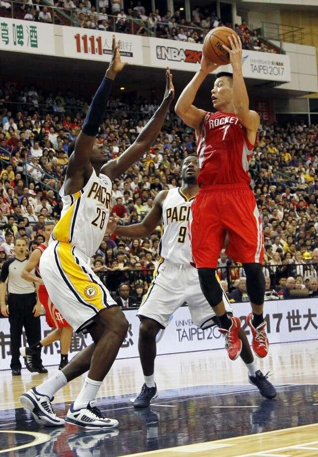 NBA Houston Rockets Jeremy Lin (7) takes a jump shot over Indiana Pacers Ian Mahinmi (28) during a preseason game in Taipei, Taiwan, Sunday, Oct. 13, 2013. The Rockets beat the Pacers 107-98. (AP Photo/Wally Santana) Photo: Wally Santana, Associated Press
