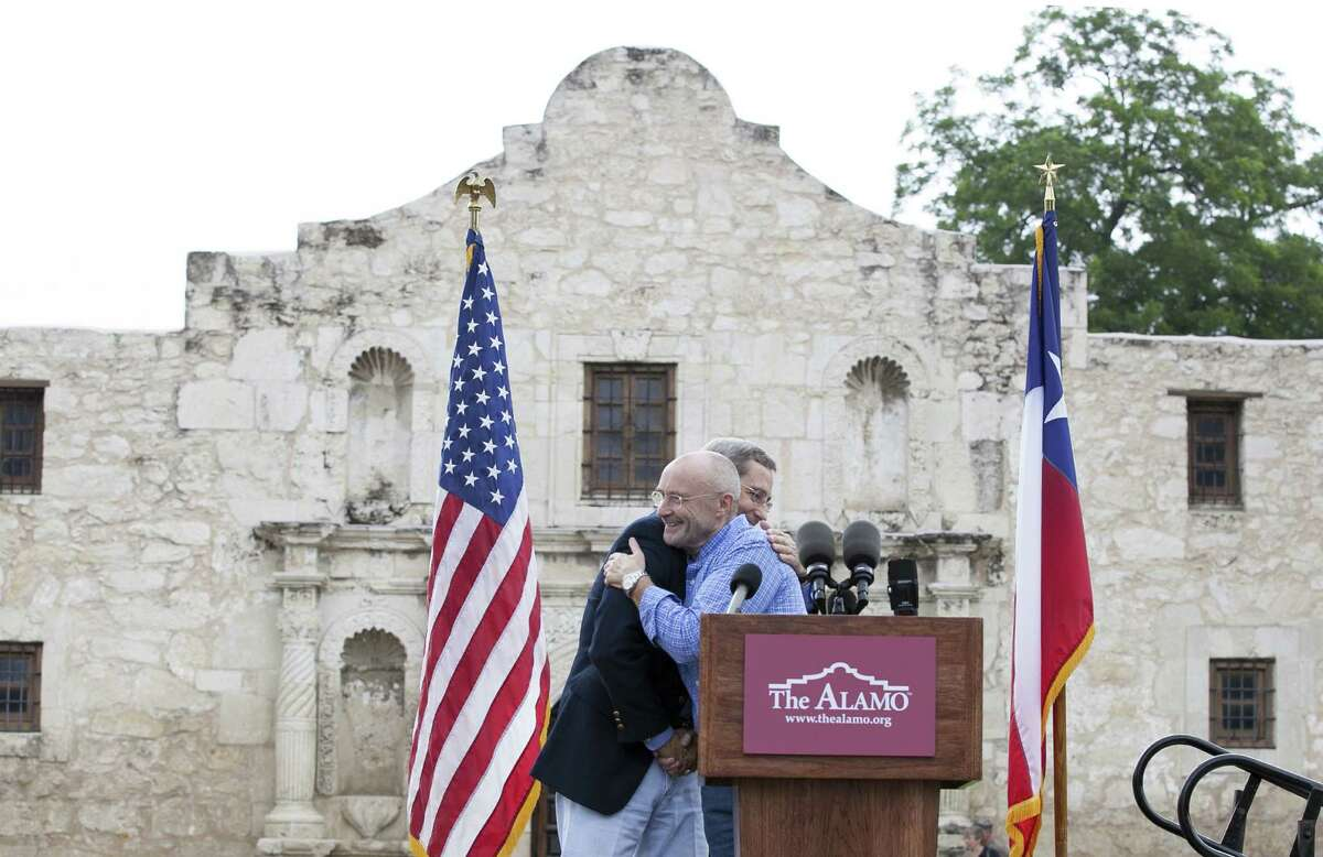 Texas Land Commissioner Jerry Patterson and singer Phil Collins embrace during the remarks in front of the Alamo.