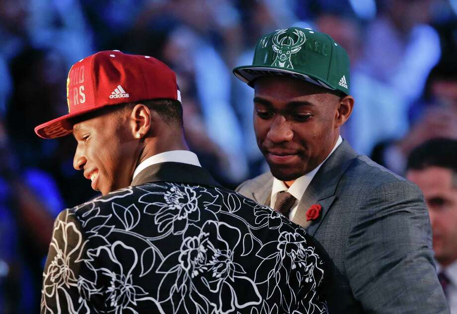Andrew Wiggins, left, and Jabari Parker stop for television interviews after being selected as the top two picks in the 2014 NBA draft, Thursday, June 26, 2014, in New York. Wiggins was selected number one by the Cleveland Cavaliers and Parker was chosen number two by the Milwaukee Bucks. (AP Photo/Kathy Willens)  ORG XMIT: NYJJ113 Photo: Kathy Willens / AP