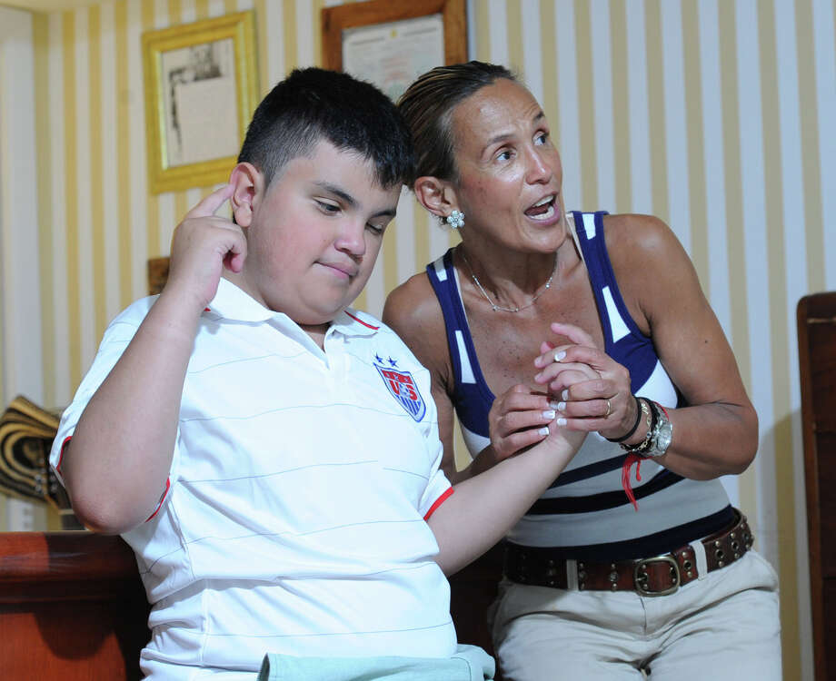 11-year-old David Tovar Jr. and his mother, Libby Tovar, right, watch the World Cup soccer match between Germany and the United States at their Greenwich home, Thursday, June 26, 2014. David Jr. is blind and a Special Olympic athlete who loves the World Cup Soccer Tournament. Although Team USA lost 1-0 to Germany, they still advanced to the knockout stage of the tournament called the round of sixteen. Photo: Bob Luckey / Greenwich Time