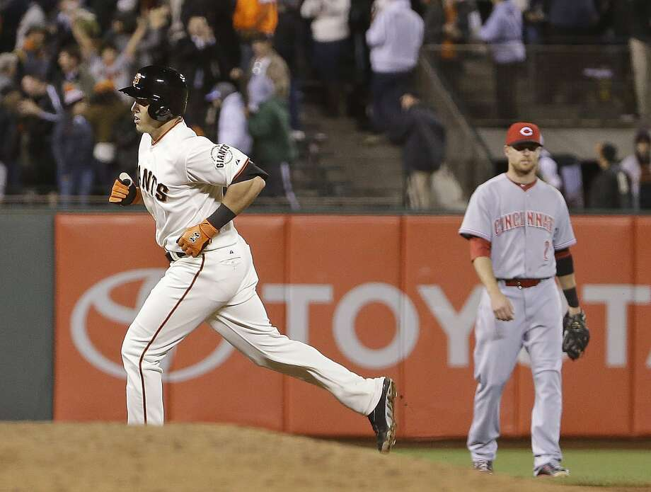 San Francisco Giants' Adam Duvall circles the bases after hitting a home run off Cincinnati Reds starting pitcher Mike Leake in the seventh inning of their baseball game Thursday, June 26, 2014, in San Francisco. Duvall was making his major league debut in the game. At right is Cincinnati Reds shortstop Zack Cozart. (AP Photo/Eric Risberg) Photo: Eric Risberg, Associated Press