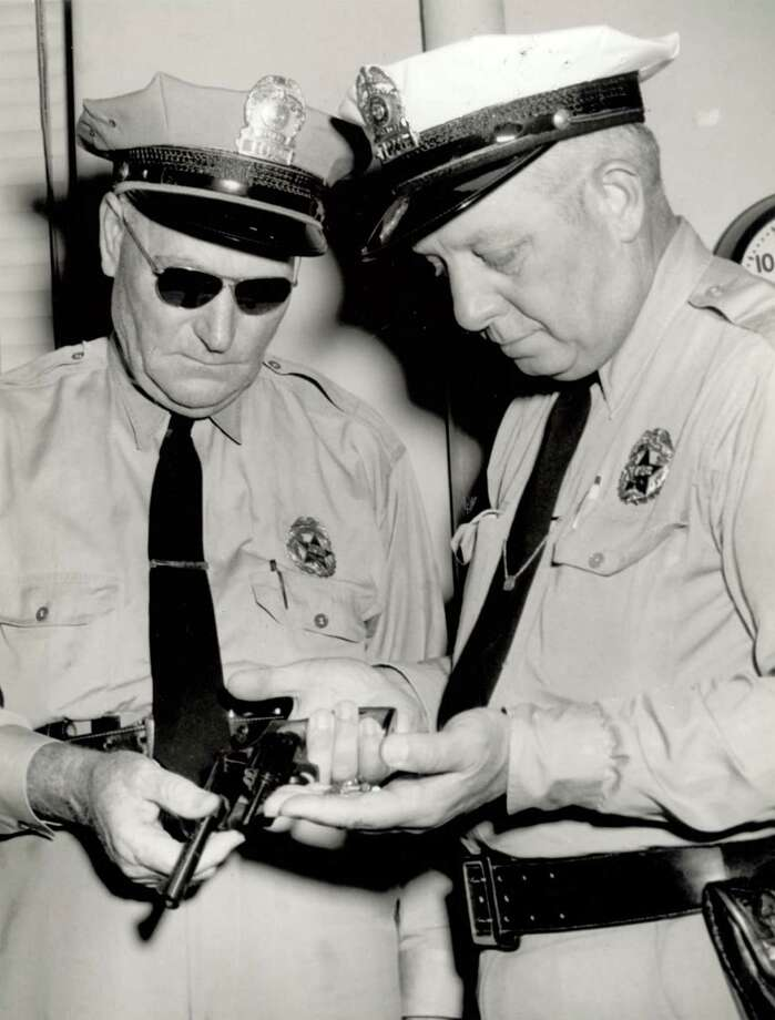Beaumont police officers inspect the pistol Lee Wesley  Banjo Red  Marshall used to shoot Jerome A.  Jake  Giles in 1958. Photo: Enterprise File Photo