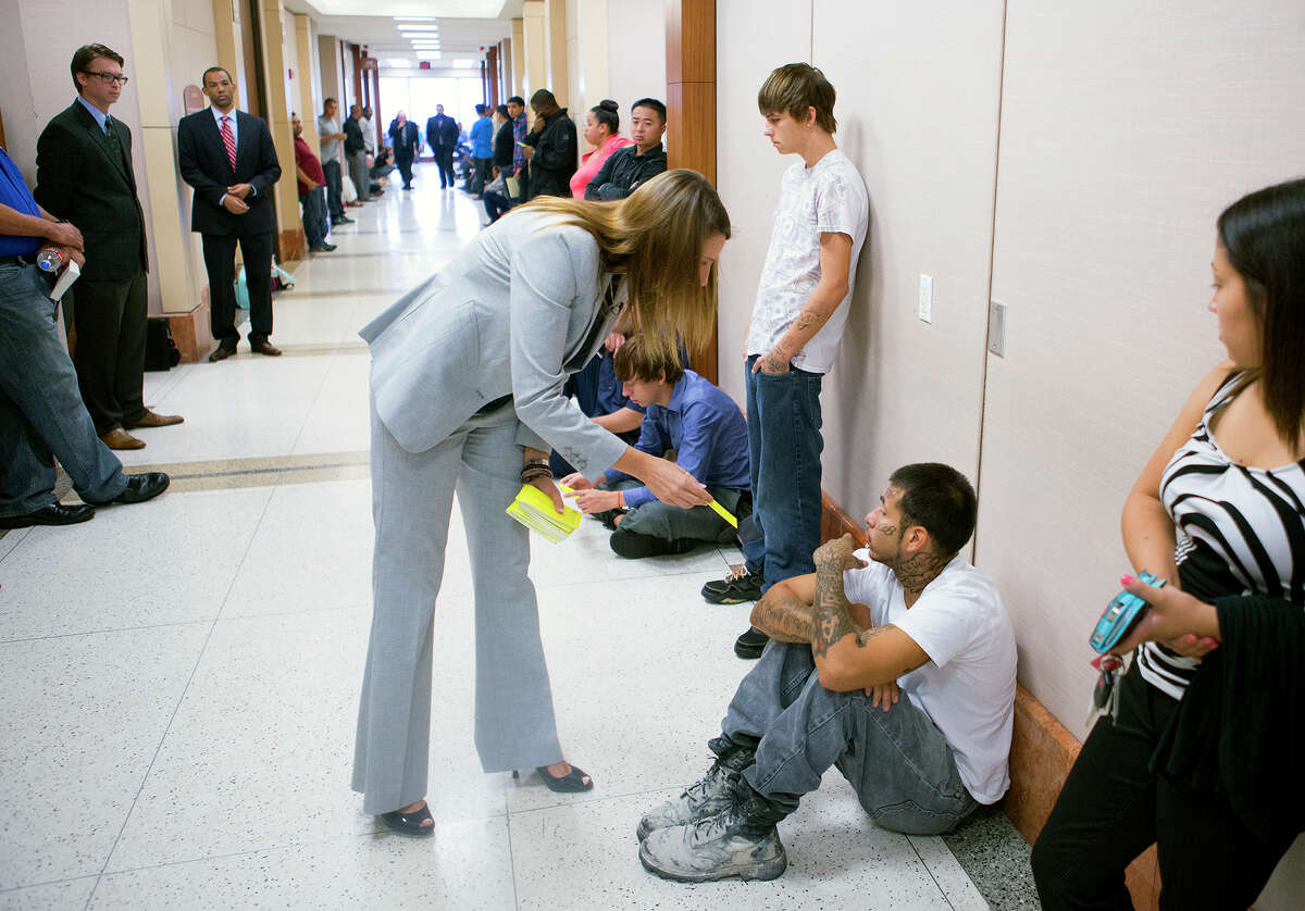Attorney JoAnne Musick hands a flyer to a patron waiting to enter court at the Harris County Criminal Courthouse, Friday, June 27, 2014, in Houston. The flyer advised defendants that a judge may be violating their constitutional rights by not appointing attorneys to their cases.