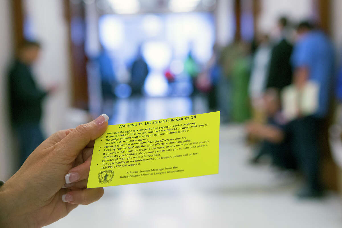 Attorney JoAnne Musick holds a flyer at the Harris County Criminal Courthouse, Friday, June 27, 2014, in Houston. The flyer advised defendants that a judge may be violating their constitutional rights by not appointing attorneys to their cases.