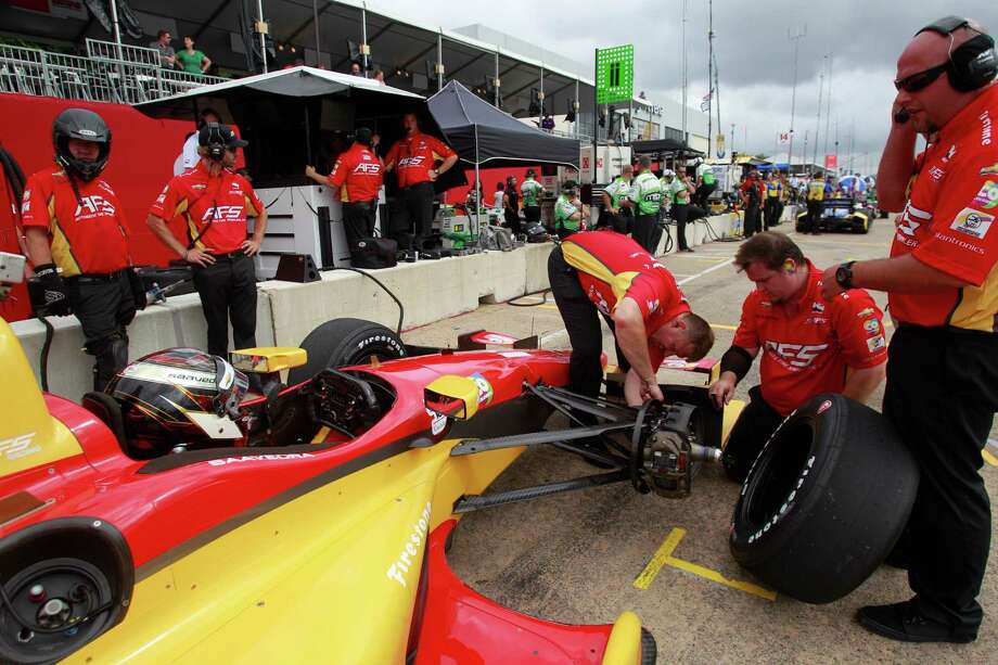 The crew for driver Sebastian Saavedra works on his car during an IndyCar practice session at the Grand Prix of Houston at NRG Park Friday, June 27, 2014, in Houston. Photo: Melissa Phillip, Houston Chronicle / © 2014  Houston Chronicle