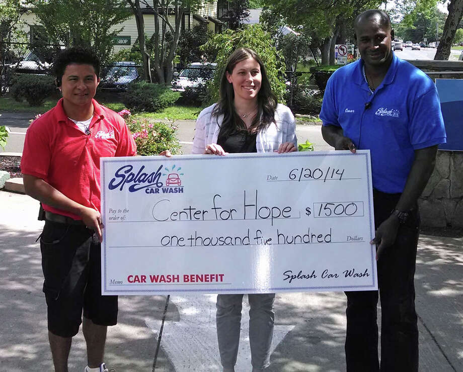 Amanda Romaniello, Family Centers' manager of clinical services for Darien and New Canaan, accepts a donation from Splash Car Wash's Oscar Moran, left, and Omar Locke for the Center for HOPE. Photo: Contributed Photo, Contributed / New Canaan News Contributed