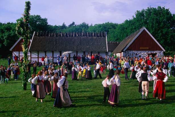 Dancing around the maypole during Midsummer Celebrations on the Himmelstorp Historic Farm grounds near Arild, on the Kulla Peninsula.