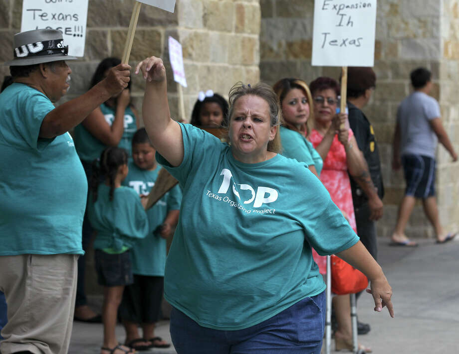 Laquita Garcia of the Texas Organizing Project (center) protests Friday June 27, 2014 in front of the Embassy Siuites Riverwalk Hotel before the arrival of U.S. Senator Ted Cruz. Cruz is speaking at a San Antonio Chamber of Commerce Luncheon. TOP is protesting about health care and immigration reform. Photo: JOHN DAVENPORT, San Antonio Express-News / ©San Antonio Express-News/John Davenport