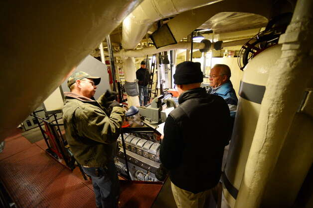 Volunteers work with Tim Rizzuto, executive director of the Destroyer Escort Historical Museum, center, in the USS Slater's engine room, March 17, 2014, at the ship's mooring dock on Broadway in Albany. The Slater was being prepared to travel to Staten Island to be put in drydock to undergo maintenance and repairs.  (Will Waldron/Times Union archive)