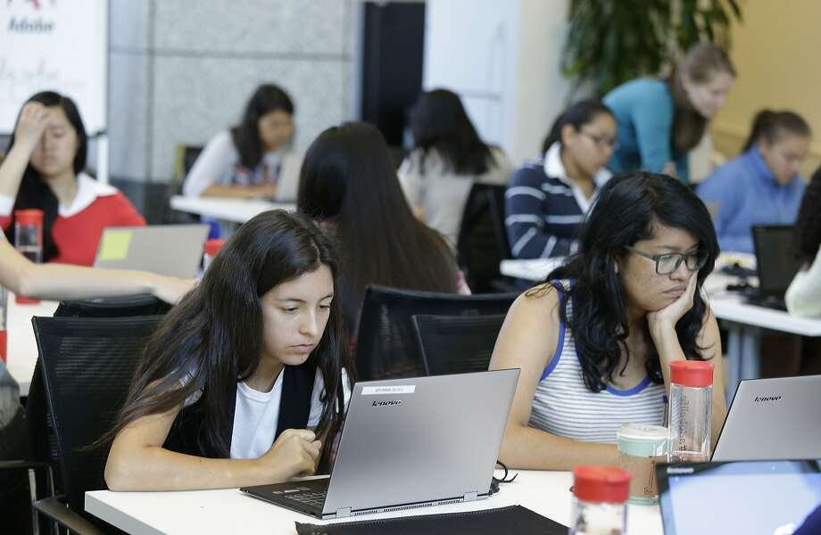 In this photo taken Wednesday, June 18, 2014, Bryanna Gilges, 15, left, and Yvonne Gonzalez, 17, right, work at completing an exercise during a Girls Who Code class at Adobe Systems in San Jose, Calif. Girls Who Code, a national non-profit organization that aims to inspire, educate and equip young women for futures in the computing-related fields, kicked off its summer program in partnership with the world's leading tech companies. The Summer Immersion Program will reach 380 high school girls across 19 classes in New York, Boston, Miami, Seattle and the Bay Area. Fewer than one percent of high school girls think of computer science as part of their future, even though it's one of the fastest growing fields in the U.S. today with a projected 4.2 million jobs by 2020, according to the Bureau of Labor Statistics.(AP Photo/Eric Risberg) Photo: Eric Risberg, Associated Press