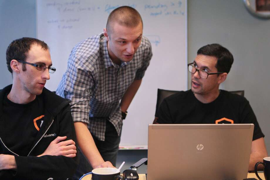 Malwarebytes founder and CEO Marcin Kleczynski (center) talks with engineers Andrew Giddings (right) and Noah Christianson-Stafford. The company develops software designed to combat sophisticated hackers. Photo: Kevin N. Hume, The Chronicle