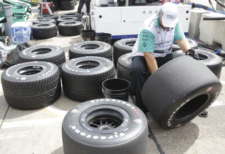 A crew member for IndyCar driver Charlie Kimball works on tires during an IndyCar practice session for the Grand Prix of Houston at NRG Park Friday, June 27, 2014, in Houston. ( Melissa Phillip / Houston Chronicle ) Photo: Melissa Phillip, Houston Chronicle