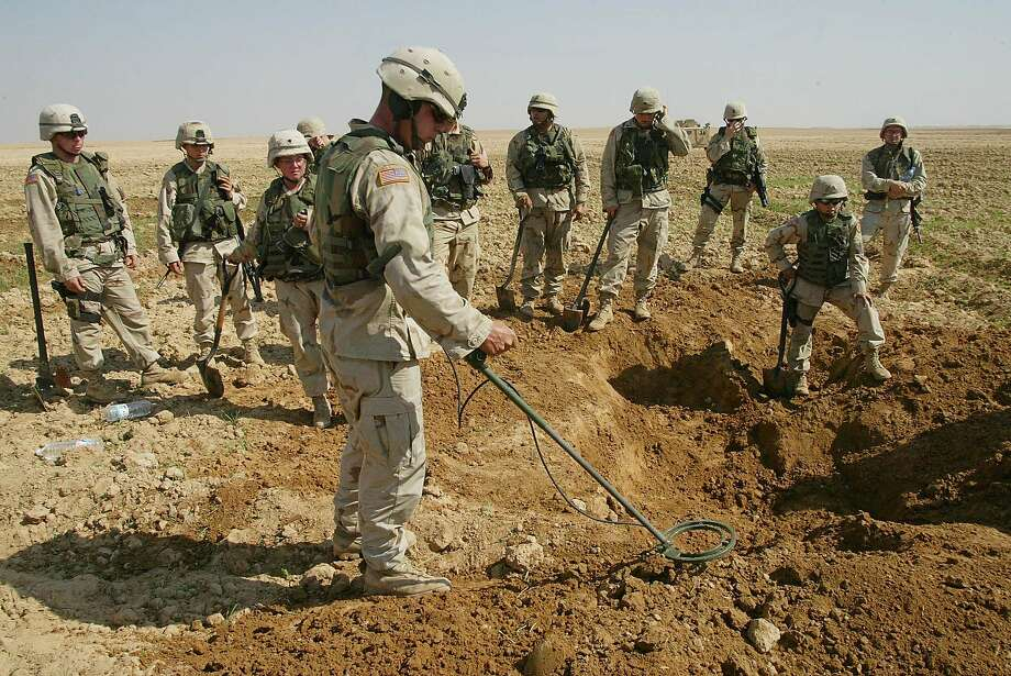 FILE This Oct. 9, 2003 file photo shows soldiers from the U.S. Army's 720th Military Police Battalion watching as a mine sweeper look for weapons in a hole they dug during a raid on a farmland just outside Tikrit, Iraq. The Obama administration announced Friday that the US will no longer produce or acquire anti-personnel land mines and plans to join an international treaty banning their use.  (AP Photo/Karel Prinsloo, File) Photo: Karel Prinsloo, Associated Press