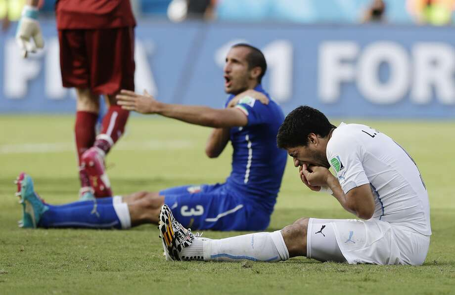 Italy's Giorgio Chiellini complains after Uruguay's Luis Suarez (right) bit his shoulder during the World Cup soccer match. Photo: Ricardo Mazalan, Associated Press