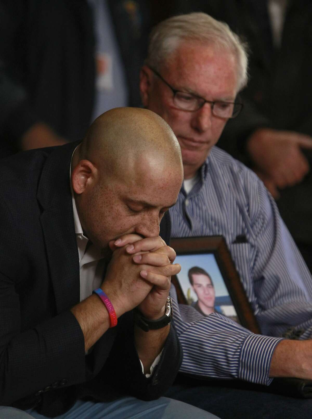 Suicide survivor Kevin Hines (left) and Mark Whitmer listen to public comments before the Golden Gate Bridge District board of directors vote unanimously in favor of erecting a suicide barrier on the iconic bridge in San Francisco, Calif. on Friday, June 27, 2014. Hines jumped from the bridge and survived but Whitmer's son Matthew took his own life after jumping from the span in 2007.