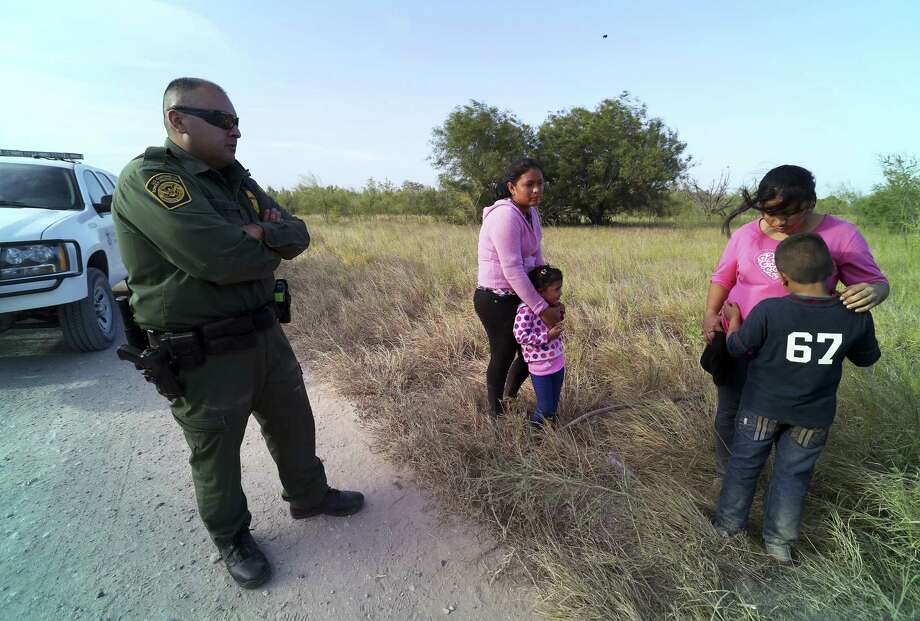 A U.S. Border Patrol agent oversees  migrants from Honduras and Guatemala found near the Rio Grande River, near McAllen. Photo: Jennifer Whitney / New York Times / NYTNS