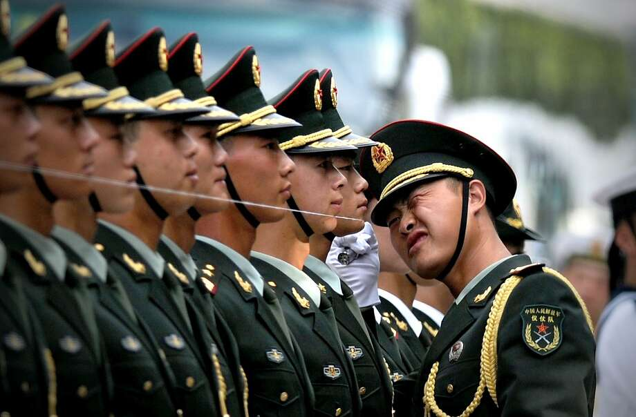 The wire test:An officer makes sure honor guards are lined up perfectly before a   welcoming ceremony for Myanmar President U Thein Sein and Chinese President Xi Jinping outside   the Great Hall of the People in Beijing. Photo: Wang Zhao, AFP/Getty Images