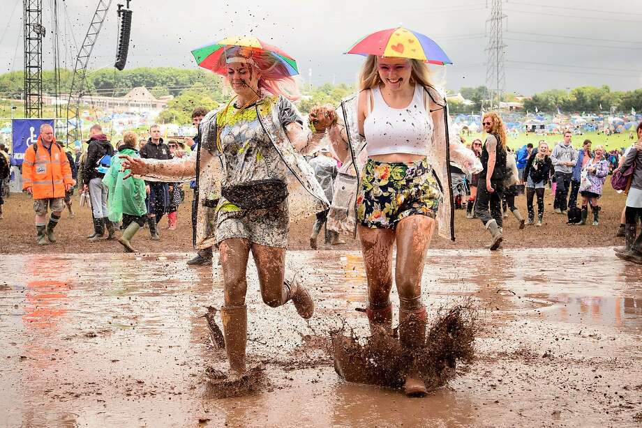These umbrella hats really keep us dry! Concert-goers run through a mud puddle on 
