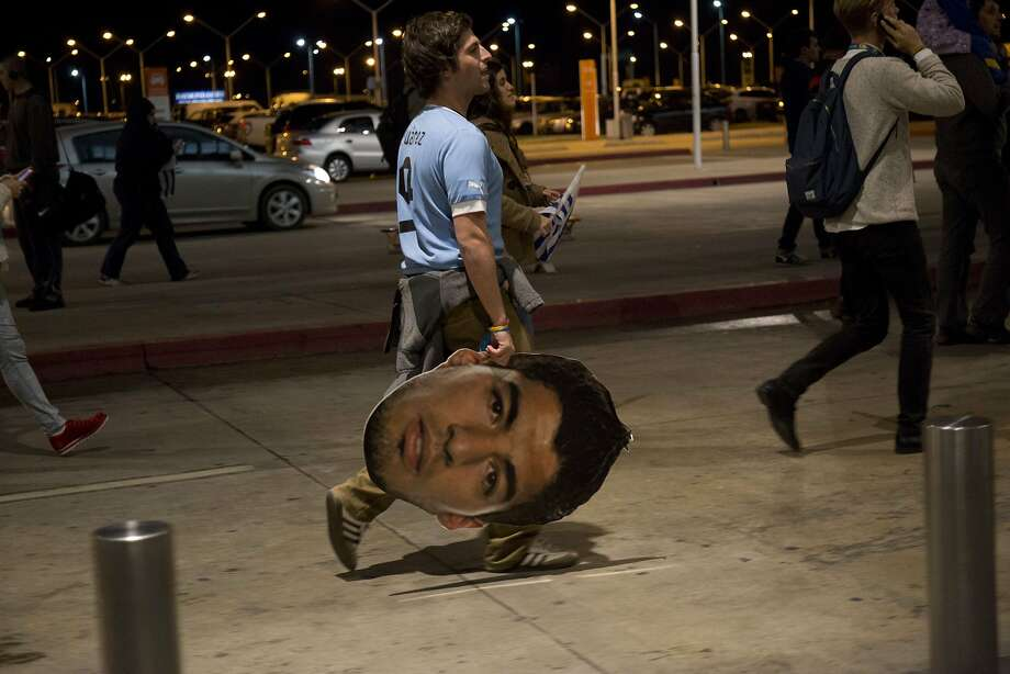 Grabbing a bite at the airport:Fans await the arrival of Luis Suarez outside Carrasco   International Airport near Montevideo after Uruguay's striker was slapped with a global four-month   ban for chewing on an opponent. It was the heaviest sanction against a player in World Cup   history. Photo: Pablo Bielli, AFP/Getty Images