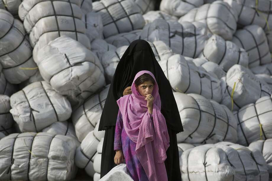 Free food for the hungry: A displaced Pakistani mother and daughter wait to get relief supplies at a distribution center 