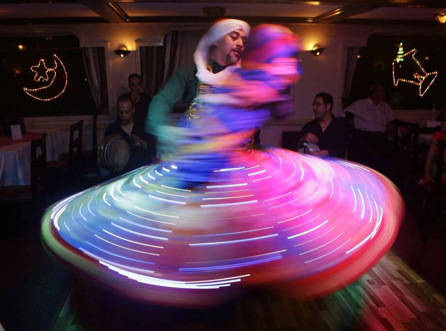 Spinning into the holiday: A whirling dervish pantomiming holding a baby spins during a performance marking the holy month of Ramadan in Cairo. Photo: Amr Nabil, Associated Press