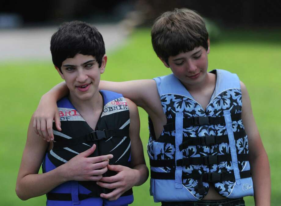 "Easton twins Ryan, left, and Julio Calish get ready to go waterskiing at the Leaps of Faith ""Soaring with the Eagles"" waterskiing day camp for the blind and visually impaired on the Housatonic River in Sandy Hook, Conn. Friday, June 27, 2014.  Ryan, who is blind, gets help from his brother Julio at the camp and in everyday life.  ""Soaring with the Eagles"" is a 4-day camp for kids ages six to 17 that teaches waterskiing, wakeboarding and tubing.  Leaps of Faith Adaptive Skiers was founded in 1992 by former waterskiing world champion Joel Zeisler with the goal to build confidence through exposure to recreational and competitve waterskiing for disabled children and adults. Photo: Tyler Sizemore / The News-Times"