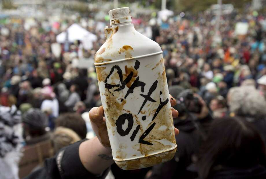 A demonstrator holds up a prop representing dirty oil during a mass sit-in in front of the British Columbia legislature in Victoria, B.C. on, Oct. 22, 2012.  Canada's government on Tuesday, June 17, 2014,  approved a controversial pipeline proposal that would bring oil to the Pacific Coast for shipment to Asia, a major step in the country's efforts to diversify its oil exports if it can overcome fierce opposition from environmental and aboriginal groups.  (AP Photo/The Canadian Press, Jonathan Hayward) Photo: Associated Press