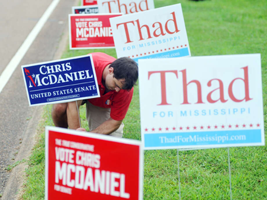 Mark Mayfield, a Mississippi Tea Party official charged with conspiring to take photos of U.S. Sen. Thad Cochran's wife inside a nursing home apparently committed suicide Friday, police said, days after Cochran won a nasty Republican primary against Tea Party darling Chris McDaniel. In this photo,Alec Jones straightens a McDaniel signs outside the voting booths at the Oxford Conference Center in Oxford, Miss., Tuesday, June 24, 2014 Photo: Bruce Newman, AP / The Oxford Eagle