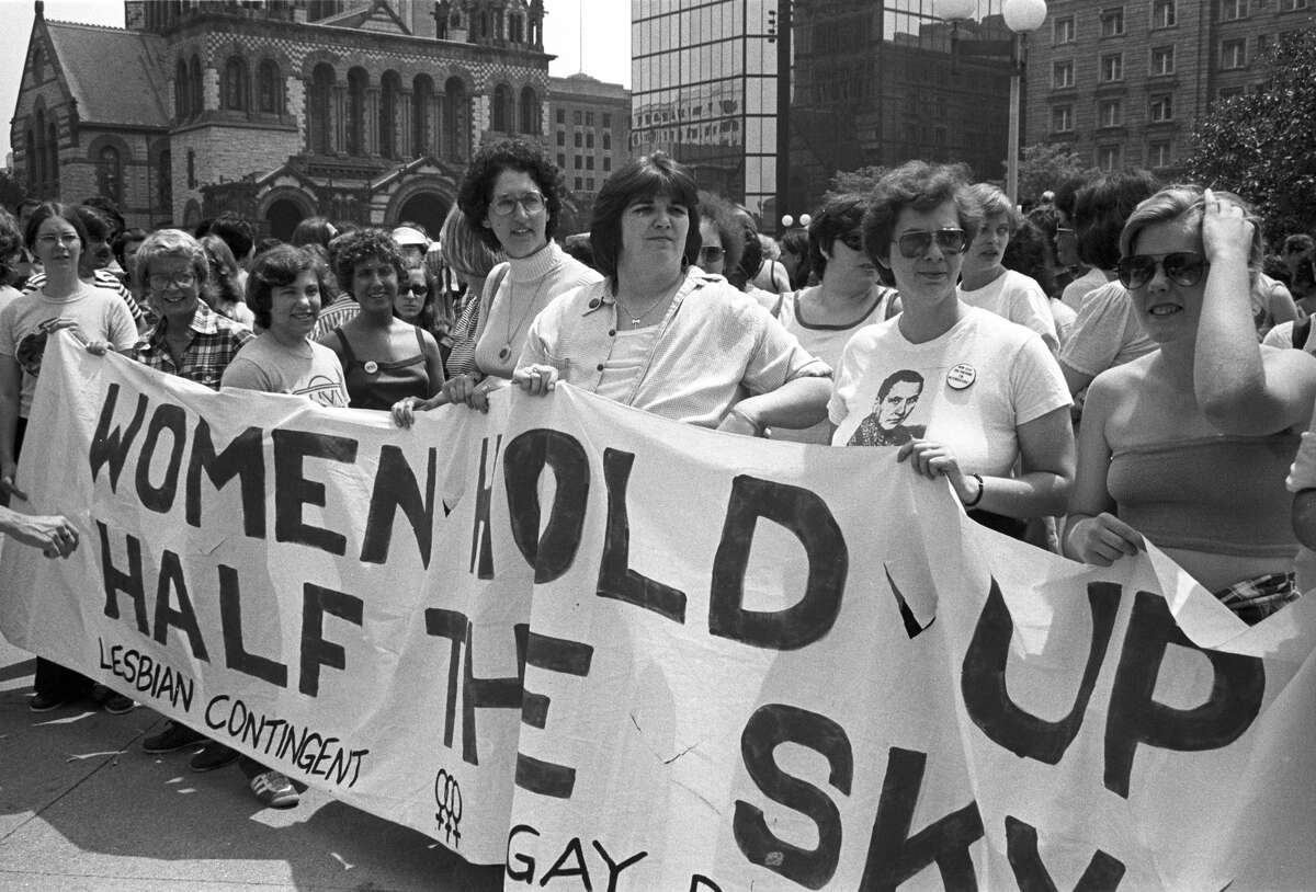 1970: View of the large crowd, some of whom are holding up handmade signs and banners, participating in a gay and lesbian pride parade in the Back Bay neighborhood of Boston, Mass.