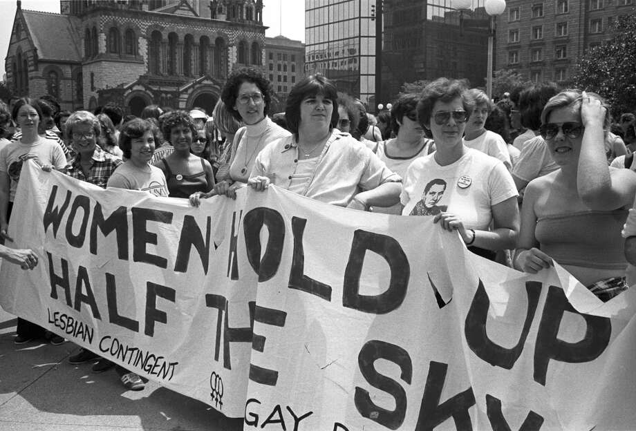 1970:View of the large crowd, some of whom are holding up handmade signs and banners, participating in a gay and lesbian pride parade in the Back Bay neighborhood of Boston, Mass.