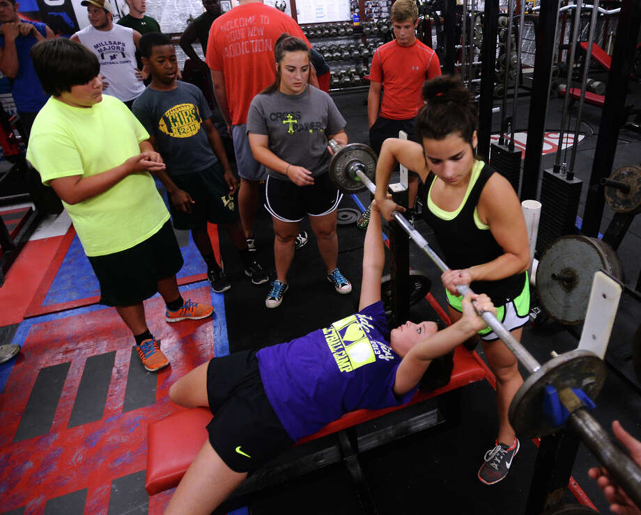 Courtney Price, 16, standing, helps Lauren Groom, 14, guide a barbell back into a resting position on a bench during a workout Tuesday. Young powerlifters exercised at Mike Denmon's Cross Trainers gym in Orange on Tuesday evening. Photo taken Tuesday 6/24/14 Jake Daniels/@JakeD_in_SETX Photo: Jake Daniels / ©2014 The Beaumont Enterprise/Jake Daniels